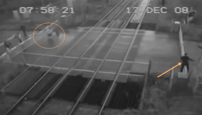 A vasúti átjárót már lezárták. Először átmegy a fekete ruhás férfi, majd egy másik is átmászik a sorompón. Nem fogsz hinni a szemednek!